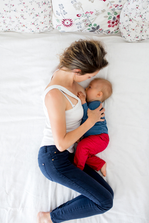 Mother and toddler baby boy, lying in bed, breastfeeding him, hugging with love, high angle shot, from above. Happy family concept
