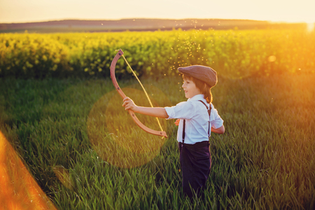 Portrait of child playing with bow and arrows, archery shoots a bow at the target on sunset