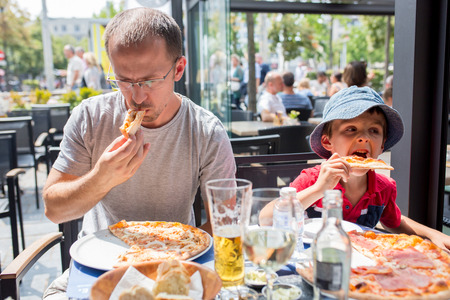 Father and child, boy and dad, eating pizza in restaurant, happily smiling Stockfoto