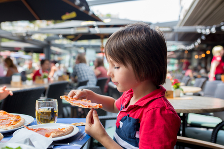 Cute child, boy, eating pizza in restaurant, happily smiling and biting Stockfoto