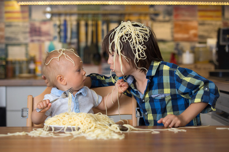 Little baby boy and his older brother, toddler child, eating spaghetti for lunch and making a mess at home in kitchen Stockfoto