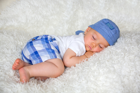 Cute baby boy, sleeping in bed with hat at home Standard-Bild - 107482092