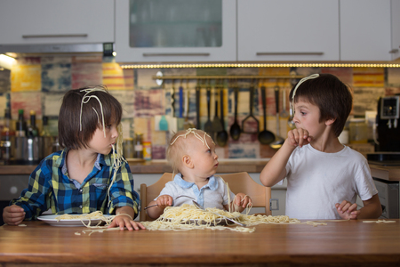Little baby boy, toddler child and his older brothers, eating spaghetti for lunch and making a mess at home in kitchen Stockfoto