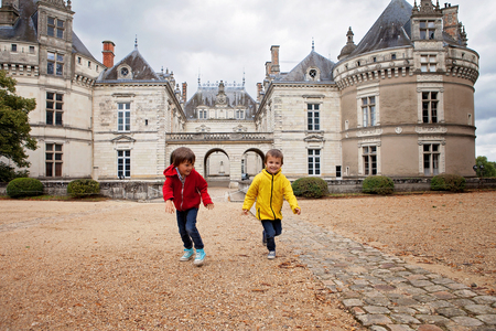 Two children, playing in the rain in front of the Le Lude castle in France Stock Photo