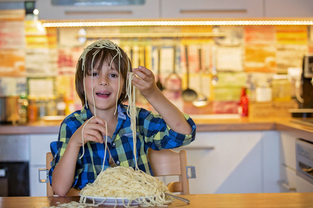 Little preschool boy, cute child, eating spaghetti for lunch and making a messat home in kitchen
