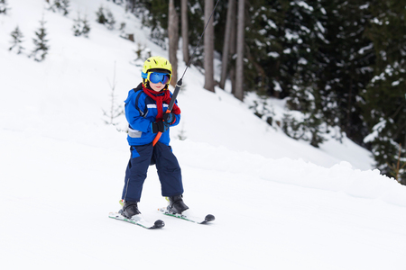 Young child, going up a hill with a surface lift, standing on the ground, using button ski lift. Little skier, learning in winter school in an Austrian resort