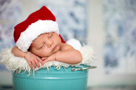 Portrait of a newborn baby boy,l wearing christmas hat, sleeping in a blue bucket, toys, christmas decoration and lantern around him, by the window, snow outside. Banco de Imagens - 107482244