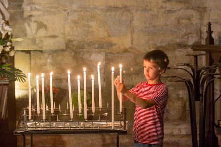 Kleiner Junge betet und setzt eine Kerze in orthodoxe Kirche, trauriges Kind mit Glauben Standard-Bild