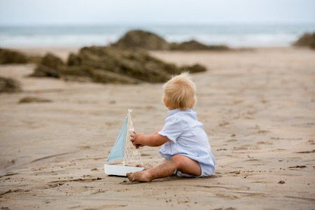 Baby boy sitting on the beach near the water and plays with a toy ship and teddy bear Banque d'images - 107482149