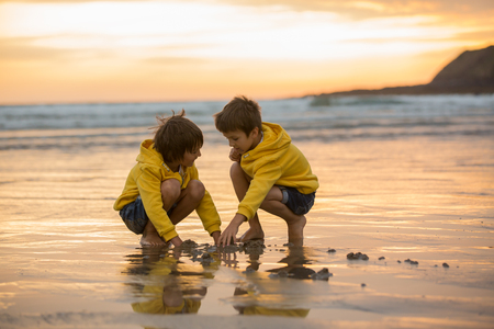 Two beautiful children, boy brothers, playing on the beach with sand and running in the water on sunset, Devon, England