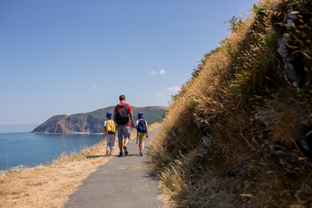 Father and two boys, family walking on a small path along the stunning Devonshire coastline near Lynmouth in Devon, England, UK 写真素材