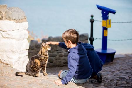 Cute child, boy, caressing cat on the street Stok Fotoğraf