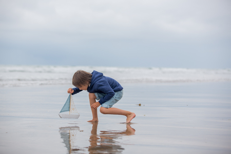 Child plays with sand on beach. Cute preschool boy with toy ship on beach. Stormy seaside sgore and kid playing on summer holiday Stock fotó