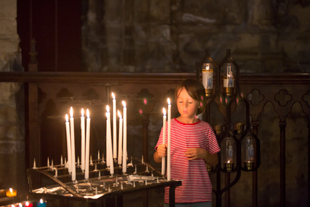 Little boy prays and puts a candle in Orthodox Church, sad kid with faith Foto de archivo