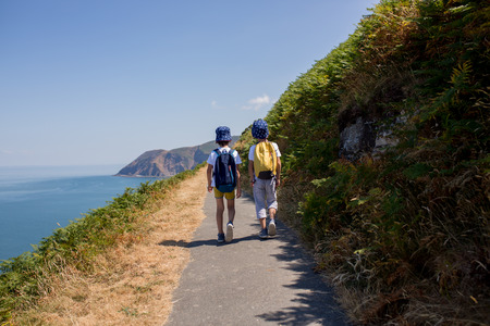Preschool children, waling on a coastline path in Deconshire, enjoying the scenery view in the summer 写真素材