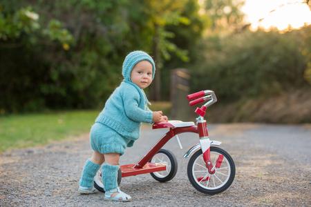 Nettes Kleinkindkind, Junge, spielend mit Dreirad im Hinterhof, Kind reitet Fahrrad auf Sonnenuntergang Standard-Bild