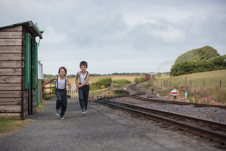 Beautiful children, dressed in vintage clothes, enjoying old steam train on a hot summer day in England