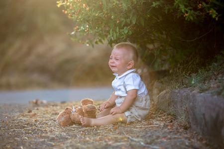 Niño pequeño triste, sosteniendo un oso de peluche, sentado solo en una carretera en el parque, llorando de tristeza, lágrimas