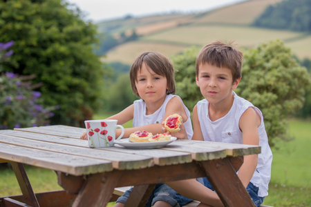 Mother and three children, having afternoon tea in the backyard of their house, beautiful landscape view of North Devon behind them