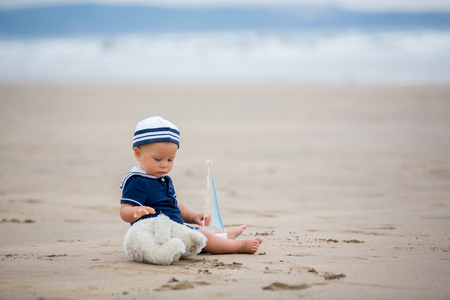 Baby boy sitting on the beach near the water and plays with a toy ship and teddy bear Stock Photo