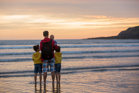 Young father with his beautiful children, enjoying the sunset over the ocean on a low tide in Devon, England Stock Photo