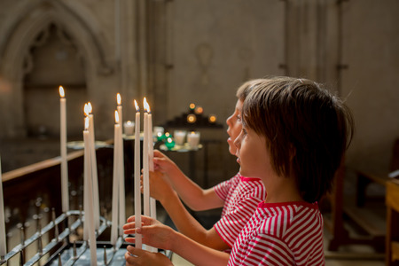 Little boy prays and puts a candle in Orthodox Church, sad kid with faith Banco de Imagens