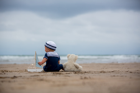 Baby boy sitting on the beach near the water and plays with a toy ship and teddy bear Stockfoto