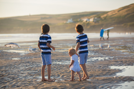 Children, beautiful boy brothers, watching and feeding seagulls on the beach on sunset Stock Photo - 107472575