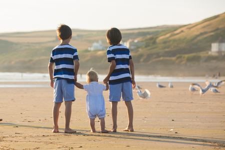 Children, beautiful boy brothers, watching and feeding seagulls on the beach on sunset Stock Photo - 107472523