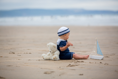 Baby boy sitting on the beach near the water and plays with a toy ship and teddy bear Banque d'images - 107472469