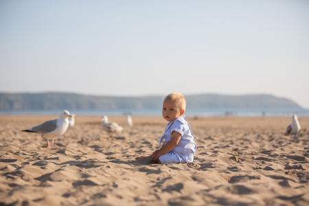 Cute baby boy, adorable child, playing with seagulls at the edge of the ocean coast Stock Photo