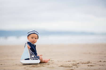 Baby boy sitting on the beach near the water and plays with a toy ship and teddy bear Banque d'images - 107472440