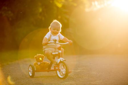 Bambino sveglio del bambino, ragazzo, che gioca con il triciclo nel cortile, bicicletta di guida del bambino sul tramonto