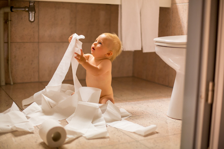 Toddler baby boy, child ripping up with toilet paper in bathroom 写真素材 - 107472242