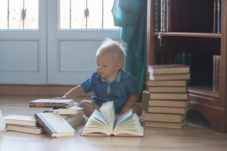 Baby child reading a book at home. Boy studying on blue background