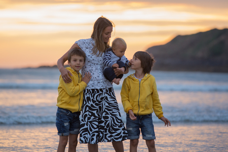 Young mother with her beautiful children, enjoying the sunset over the ocean on a low tide in Devon, England