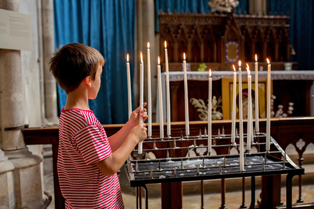 Little boy prays and puts a candle in Orthodox Church, sad kid with faith Stock Photo