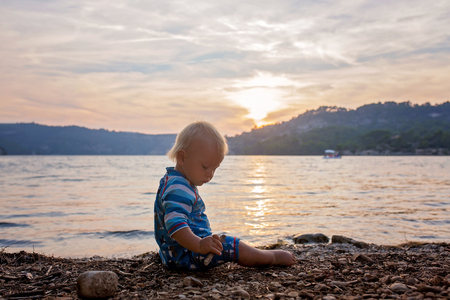 Cute child, toddler boy, enjoying the sunset over a lake, summertime Stock Photo
