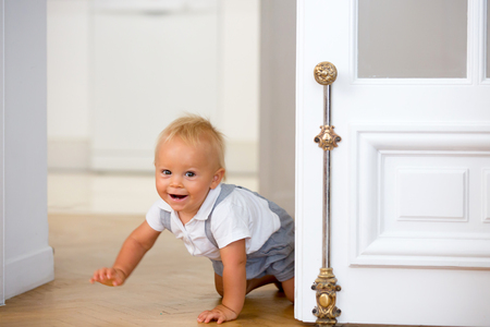 Little cute baby child, boy, crawling from behind a door at home Stock Photo