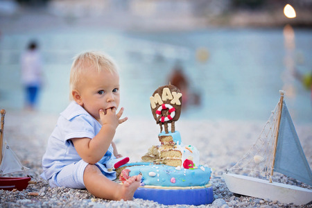 Sweet baby boy, celebrating on the beach first birthday with sea theme cake and sea decoration Reklamní fotografie