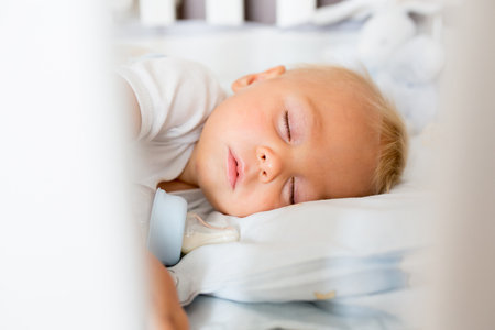 Cute little baby boy, sleeping with bottle with formula milk. Tired child in baby cot bed Stock Photo