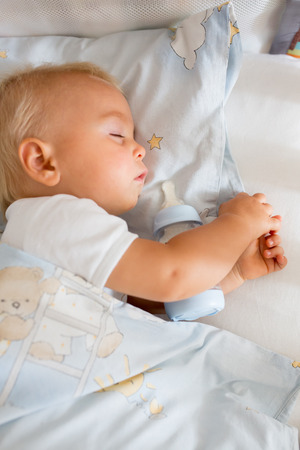 Cute little baby boy, sleeping with bottle with formula milk. Tired child in baby cot bed Reklamní fotografie
