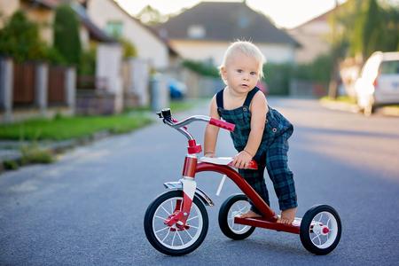 Nettes Kleinkindkind, Junge, spielend mit Dreirad auf der Straße, Kind, das Fahrrad auf Sonnenuntergang reitet