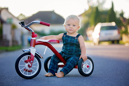 Cute toddler child, boy, playing with tricycle on the street, kid riding bike on sunset Foto de archivo - 108209357