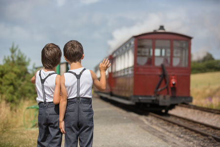 Beautiful children, dressed in vintage clothes, enjoying old steam train on a hot summer day in England Banco de Imagens - 108209445