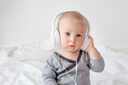 Cute little toddler baby boy listening music with head phones in bed Reklamní fotografie