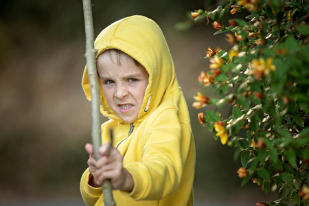 Preschool boy, shooting with bow and arrow on sunset in garden