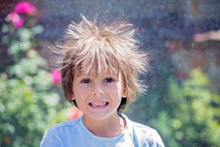 Mignon petit garçon aux cheveux d'électricité statique, ayant son drôle de portrait pris à l'extérieur sur un trampoline