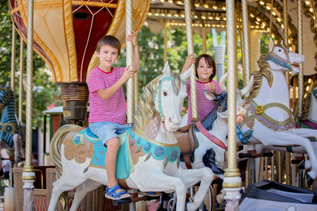 Children going on Merry Go Round, kids play on carousel in the summer