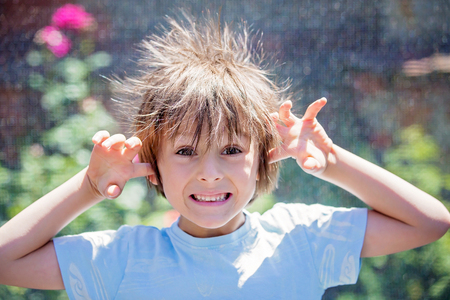 Cute little boy with static electricy hair, having his funny portrait taken outdoors on a trampoline 스톡 콘텐츠